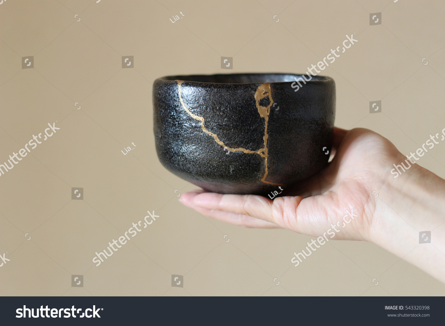 An image of a small, black Japanese bowl with a crack running through it. The crack has been mended or filled in with gold.
